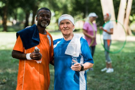 Photo for Selective focus of sportive multicultural retired men holding bottles with water - Royalty Free Image