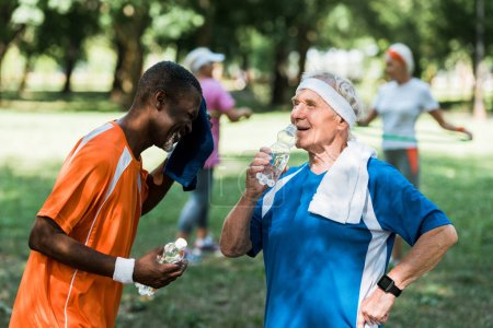 Photo for Selective focus of sportive multicultural retired men holding bottles with water near senior women - Royalty Free Image
