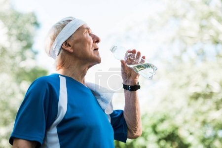 Photo for Low angle view of senior man holding bottle with water - Royalty Free Image