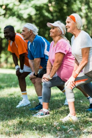 Photo for Selective focus of cheerful senior and multicultural people doing stretching exercise on grass - Royalty Free Image