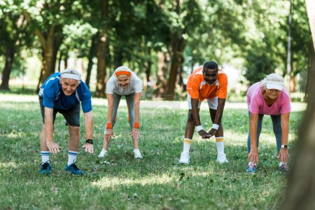 Photo for Selective focus of happy multicultural pensioners doing stretching exercise on grass - Royalty Free Image