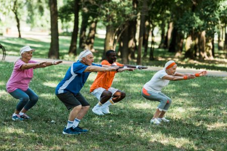 selective focus of multicultural retired men and women doing sit ups on grass