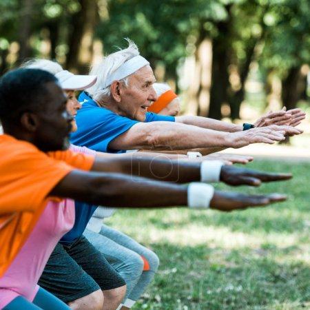 Foto de Enfoque selectivo de hombre de la tercera edad alegre con las manos extendidas cerca de los pensionistas multiculturales - Imagen libre de derechos