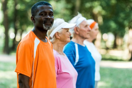selective focus of cheerful retired african american man looking at camera near multicultural pensioners