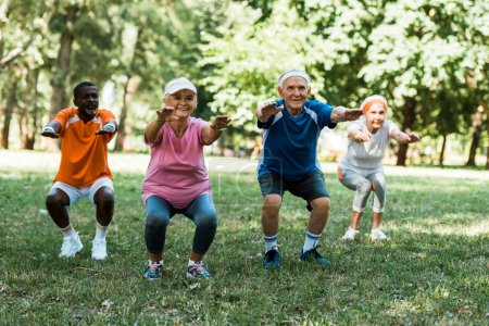 Photo for Multicultural pensioners doing sit ups in park on green grass - Royalty Free Image
