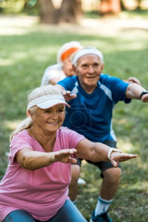 selective focus of happy multicultural retired people doing sit ups on grass