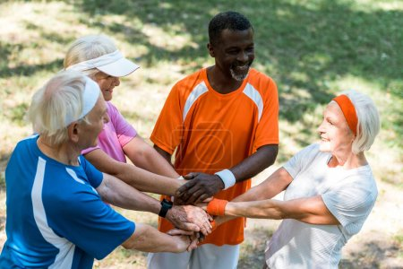 Photo pour Overhead view of cheerful multicultural senior men and women putting hands together - image libre de droit