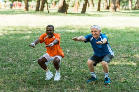 Photo for Happy retired and multicultural med doing sit ups on grass - Royalty Free Image