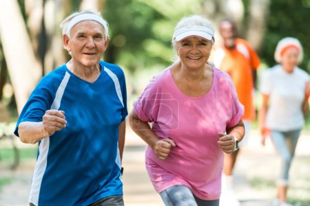 Photo for Selective focus of cheerful retired couple exercising outside - Royalty Free Image