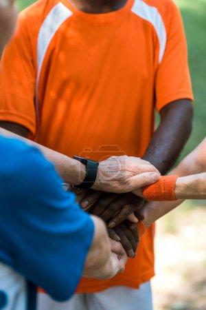 Foto de Vista recortada de hombres y mujeres jubilados multiculturales poniendo las manos juntas - Imagen libre de derechos