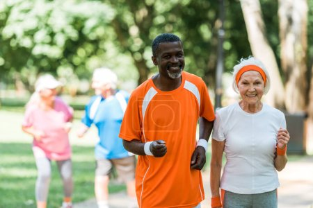 Photo for Selective focus of african american senior man and retired woman exercising near pensioners outside - Royalty Free Image