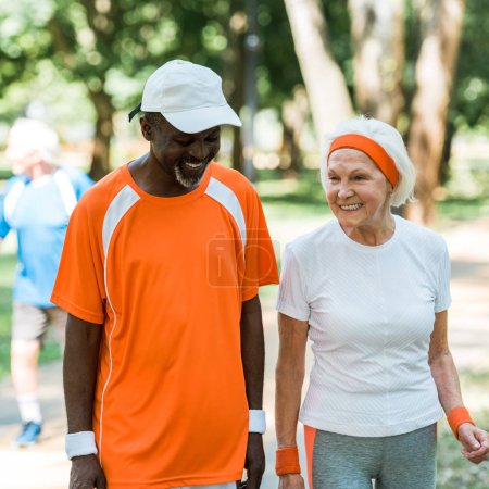 Photo for Selective focus of african american senior man and cheerful retired woman smiling ouside - Royalty Free Image