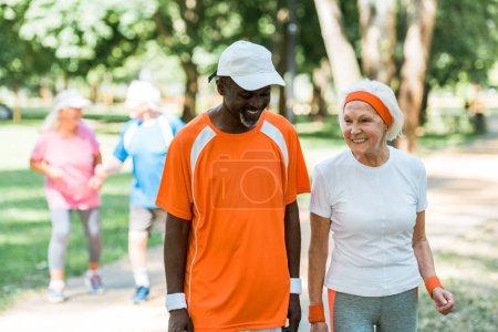 Foto de Enfoque selectivo de afroamericano hombre mayor y alegre mujer jubilada sonriendo cerca de los pensionistas ouside - Imagen libre de derechos