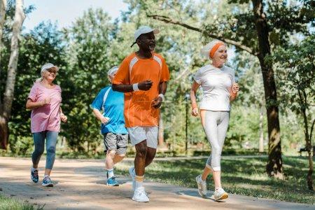 Foto de Hombres y mujeres multiculturales y jubilados felices corriendo en el parque - Imagen libre de derechos