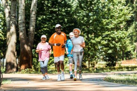 Photo pour Hommes et femmes multiculturels et seniors en sportswear courant en stationnement - image libre de droit