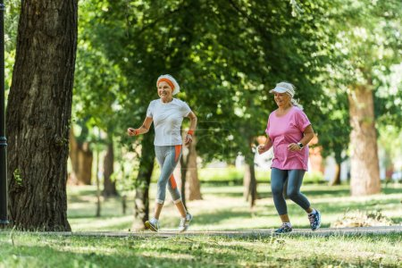 selective focus cheerful senior women in sportswear jogging in park