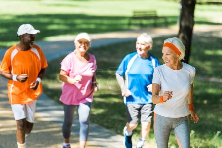 Photo for Selective focus of happy retired woman running with multicultural pensioners in park - Royalty Free Image