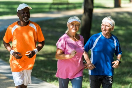 Photo pour Foyer sélectif de la femme heureuse retraitée courant avec des hommes multiculturels - image libre de droit