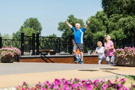 Photo pour Foyer sélectif de heureux retraités célébrant triomphe près des retraités multiculturels dans le parc - image libre de droit