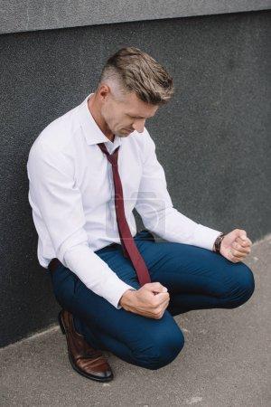 Photo pour Bouleversé homme d'affaires assis avec les poings serrés à l'extérieur - image libre de droit