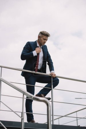 selective focus of upset businessman in suit standing outside and touching tie