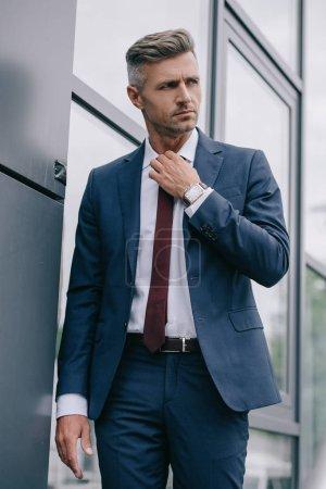 Photo pour Homme d'affaires sérieux en tenue formelle touchant cravate à l'extérieur près du bâtiment - image libre de droit