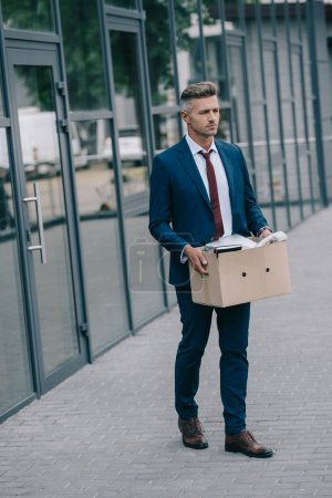 Photo for Dismissed businessman walking near building and holding carton box - Royalty Free Image