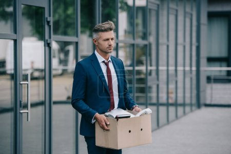 Photo for Sad and fired businessman standing near building and holding carton box - Royalty Free Image