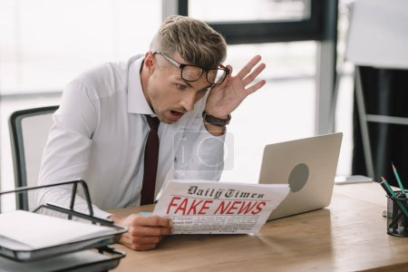 Photo pour Foyer sélectif de l'homme d'affaires émotionnel touchant des lunettes tout en lisant le journal avec de fausses nouvelles - image libre de droit