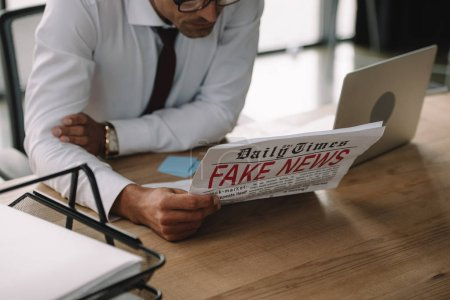 Photo for Cropped view of businessman in glasses reading newspaper with fake news - Royalty Free Image