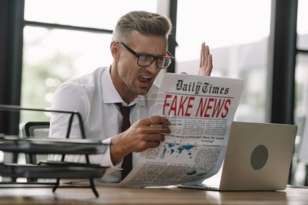Photo for Selective focus of emotional businessman in glasses gesturing while reading newspaper with fake news - Royalty Free Image