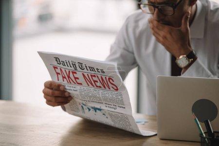Photo pour Choqué homme d'affaires dans des lunettes couvrant la bouche tout en lisant le journal avec de fausses nouvelles - image libre de droit