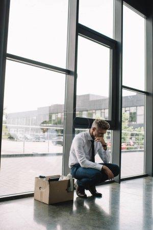 Photo pour Homme d'affaires congédié couvrant la bouche tout en s'asseyant la boîte de carton dans le bureau - image libre de droit