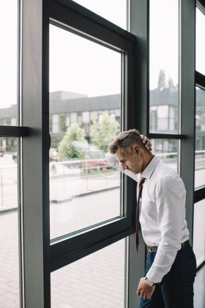 Photo for Upset businessman in suit standing near windows in office - Royalty Free Image