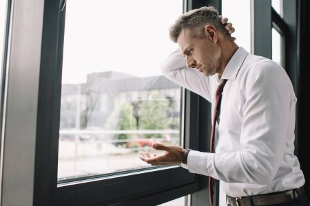 upset man in suit gesturing while standing near windows