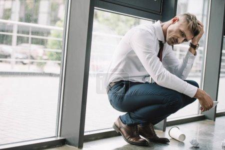 Photo pour Homme d'affaires frustré s'asseyant près des fenêtres et retenant le smartphone - image libre de droit