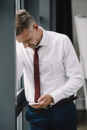 Photo for Upset businessman standing in suit and using smartphone - Royalty Free Image