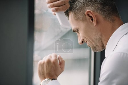 Photo for Selective focus of upset businessman holding smartphone near window - Royalty Free Image