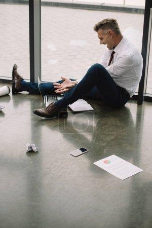 Photo pour Homme mécontent gestuelle tout en étant assis sur le sol et en regardant ordinateur portable - image libre de droit