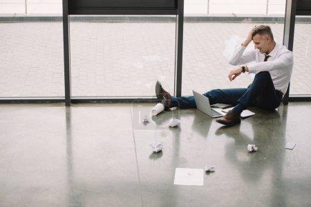 Photo pour Vue latérale de l'homme mécontent assis sur le sol et regardant ordinateur portable - image libre de droit