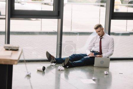 Foto de Enfoque selectivo del hombre de negocios escribir en portátil cerca de portátil - Imagen libre de derechos