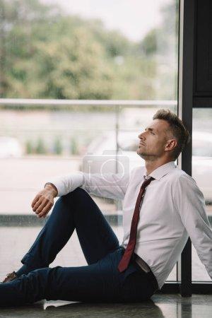 Photo pour Beau homme d'affaires s'asseyant sur l'étage près des fenêtres dans le bureau - image libre de droit