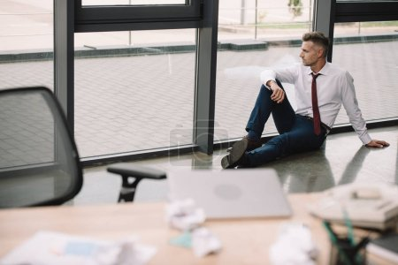 Photo for Selective focus of man sitting on floor near workplace - Royalty Free Image