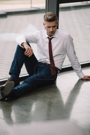 Photo pour Homme d'affaires frustré assis sur le sol près des fenêtres dans le bureau - image libre de droit