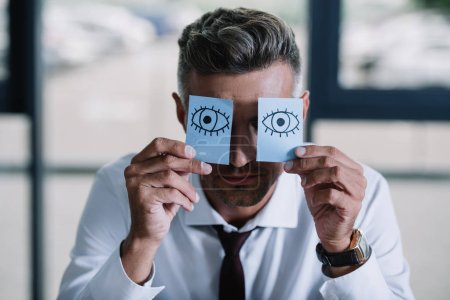 Photo for Businessman in suit holding sticky notes with drawn eyes near face - Royalty Free Image