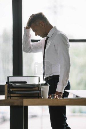 Photo pour Foyer sélectif de l'homme d'affaires bouleversé touchant la tête près du bureau dans le bureau - image libre de droit