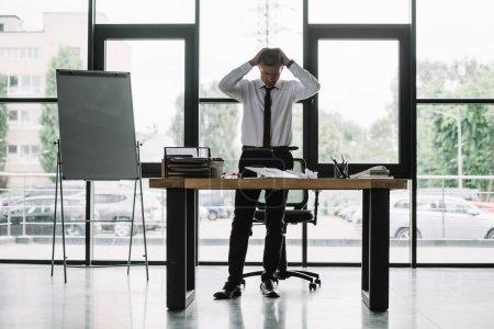 Photo pour Homme d'affaires touchant la tête tout en regardant la table dans le bureau - image libre de droit