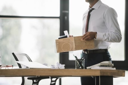 cropped view of dismissed businessman holding wooden box in modern office