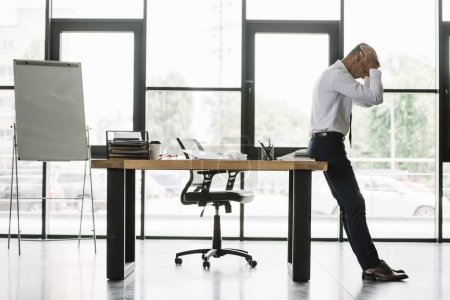 Photo pour Beau homme d'affaires touchant la tête tout en restant près de la table dans le bureau moderne - image libre de droit