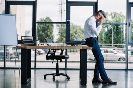 Photo pour Homme d'affaires touchant la tête tout en restant près de la table dans le bureau moderne - image libre de droit
